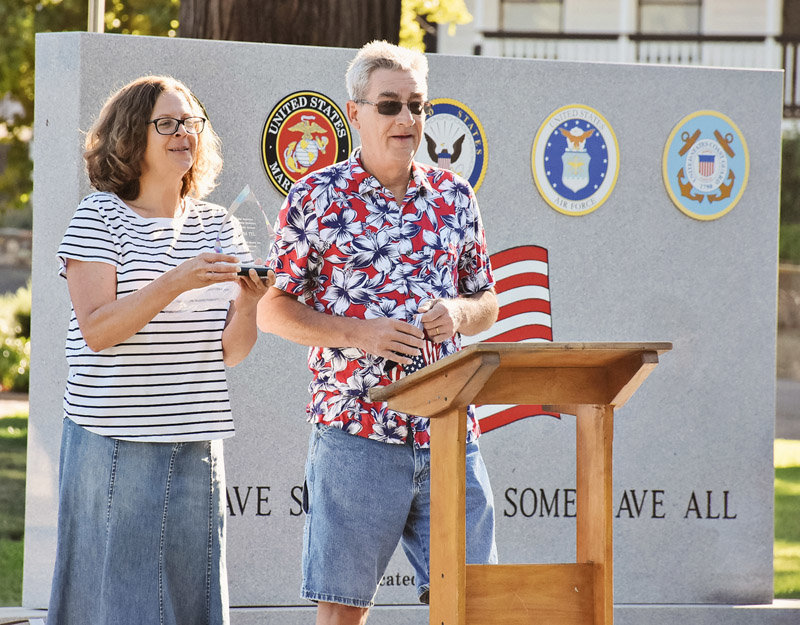 Greg Little, who co-owns the Mariposa Gazette with his wife, Nicole (also shown), presents recognition plaques during the July 4, 2020 dedication of the new Mariposa County Veterans Memorial.