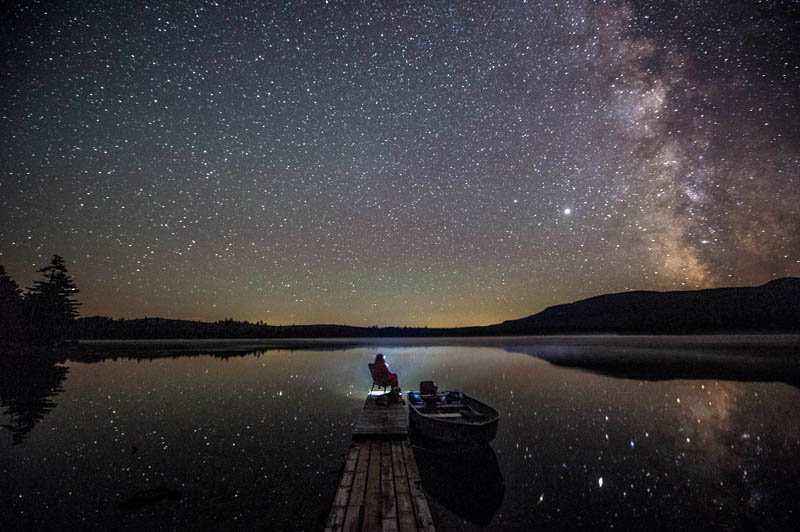 A camper takes in the night air and sky from the end of the lone dock on the remote Rock Pond in the Unorganized Territories of the northwest mountains in Maine on Aug. 15, 2020.