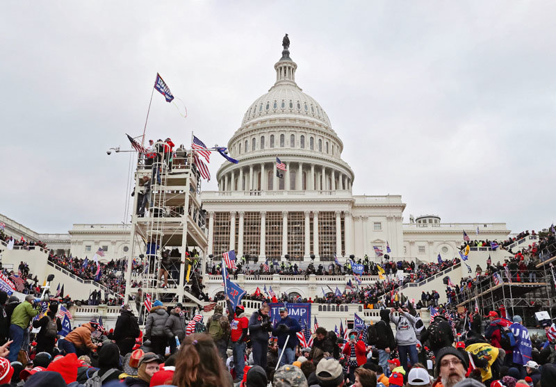 A mob of Trump supporters climb scaffoldings and take to the steps of the U.S. Capitol building in Washington D.C. on Jan. 6, 2021. Rioters breached the building following a rally as Congress was preparing to certify President-elect Joe Biden's victory.