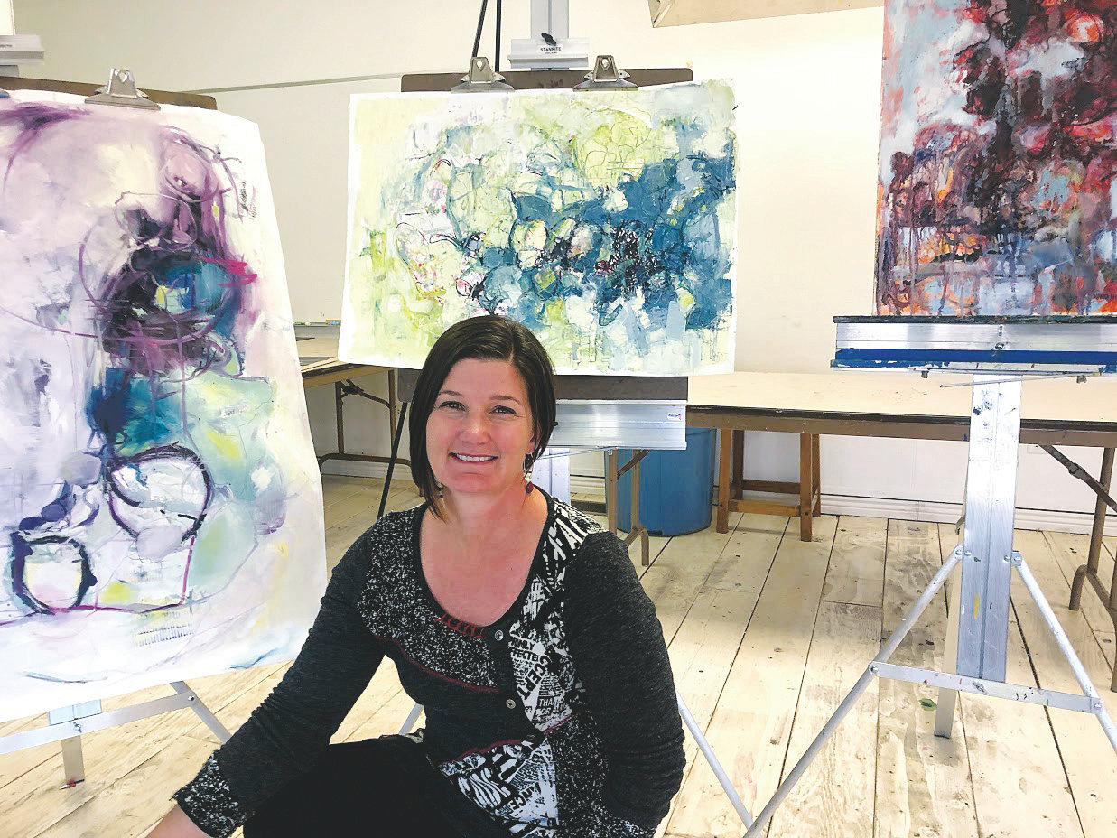 Nikki Nienhuis sits with her artwork in Foothills Art Center's Open Studio Classroom. Nienhuis of Golden is now in two Colorado galleries — Georgetown's Colorado Mountain Art Gallery and Portfolio in Breckenridge, which is a new gallery that had its grand opening on Aug. 3.