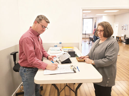 James L. White/StaffBoone County poll worker Brain Doyle signs in Valley Springs School Superintendent Judy Green during early voting Thursday.