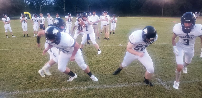 The Marshall offensive line runs a play on Friday night before its game. The Bobcats defeated Brinkley 40-34.