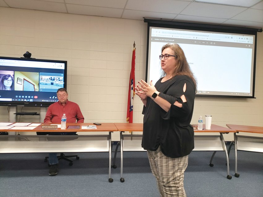 Harrison School Board president Mitch Magness listens as Rebecca Williams, the district's school-based human services and homeless liaison, describes how two grants totaling $30,000 will be used to help feed hungry students.