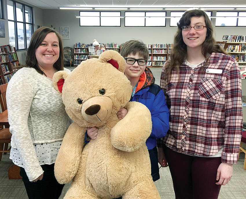 Litchfield Public Library will celebrate its first anniversary in the new building on Monday, Feb. 25. Above Stephanie Miller, Caden Wygal and Paige Davidson pose with a giant teddy bear, which will be available for photos at the library's upcoming open house.