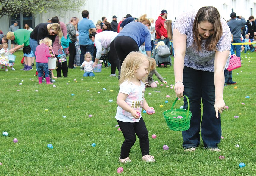 Assisted by her aunt Courtney Thull, two-year-old Waverly McDaniel of LItchfield (above) gets the hang of hunting eggs as she uses both hands to collect as many as she can.