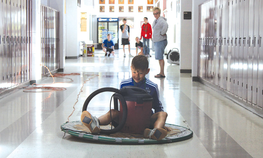 """Students in grades fourth through sixth sure had """"Phun with Physics"""" during the Litchfield Summer Gifted Academy on Tuesday morning, June 11, at Litchfield High School. Using a Shop-Vac to stay afloat, Carter Loh rides the hovercraft down the hall as his classmates and teacher, Kelley Sonneborn, watch how far he can reach."""