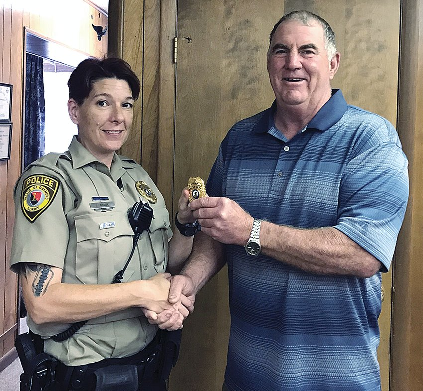 Pictured above, Mayor Dennis Held (at right) presents Raymond's new police officer Jody Grove with her new badge.