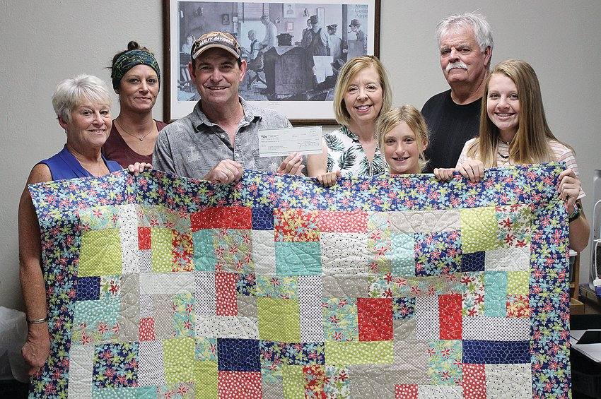 Pictured above, from the left, are mother and sister of the late Dana Shea Hodges-Denny, Kim Blackburn and Cody Hodges; lucky quilt winner Bill Schweizer; Pam Dawson of the Summer Lunch Program, who accepted an` $8,000 donation from the raffle; her daughter, Brooklyn Fisher; father, Daryl Hodges; and niece, Sophia Blankenship.