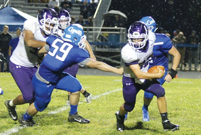 Senior quarterback Clayton Walch tries to elude the rain drops and the grasp of the Greenville defense in the second quarter of Litchfield's opening game in Greenville on Friday, Aug. 30. Walch was a bright spot for the Panthers, rushing for 78 yards on 19 carries, in Litchfield's 37-0 loss to the Comets.