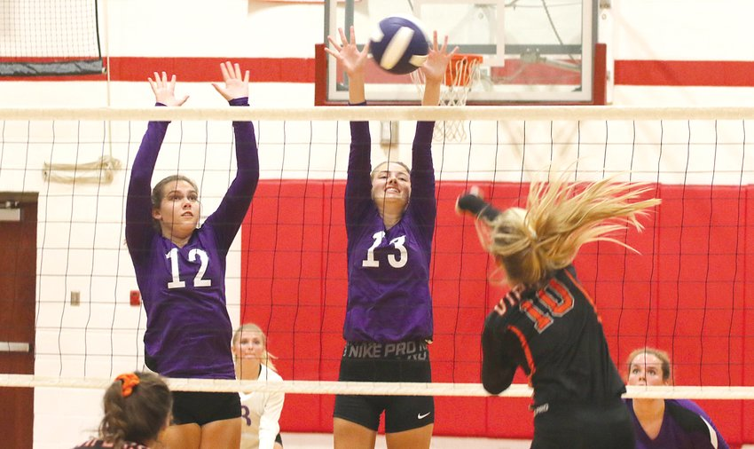 """Hillsboro's Emma Miller (#12) and Kayli Ward (#13) go up for a block during the Toppers' Montgomery County Invitational pool play game against South County on Friday, Sept. 13, in Nokomis. Hillsboro swapped out their orange and black jerseys for purple """"Team Grace"""" ones in honor of eight-year-old Grace Herschelman, who is battling infantile neuroaxonal dystrophy (INAD). The 16-team tournament raises money and awareness for INAD research in Grace's name."""