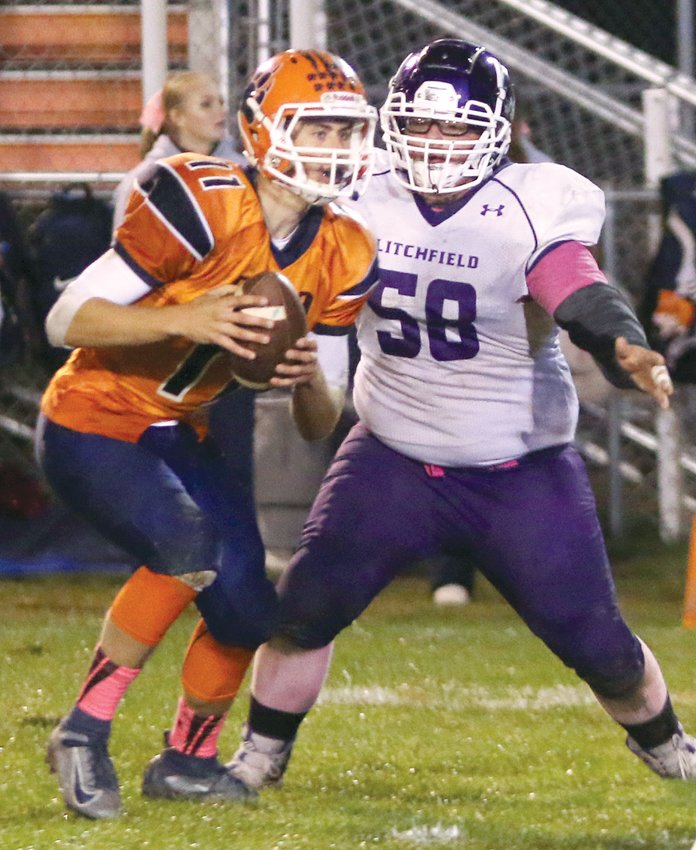 Litchfield's Austin Dewitt bears down on Pana quarterback Jonah Lauff during the Purple Panthers' 61-6 loss to the South Central Conference front-runners on Friday, Oct. 11, in Pana.