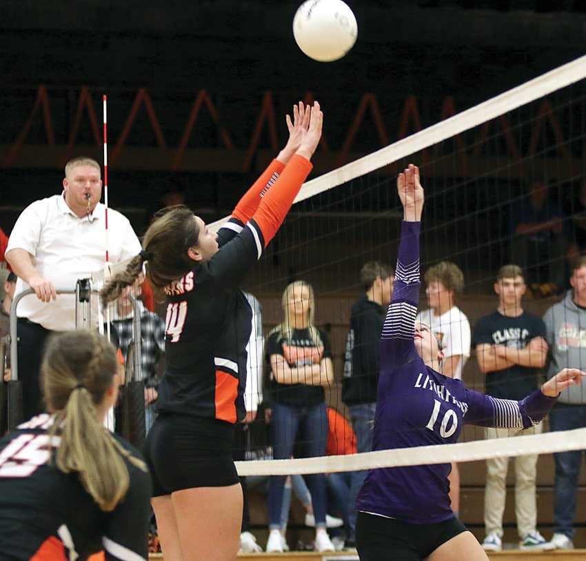 Litchfield's Devan Morgan pokes a hit over the outstretched hands of blocker Hillsboro Emily Reynolds during the clash of the county rivals on Tuesday, Oct. 22, in Hillsboro. After splitting the first two games, Hillsboro would come away with a three-set victory to stave off the Purple Panthers' upset bid.