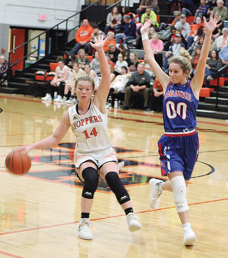 Hillsboro's Shelby Houchlei (#14) and Carlinville's Corin Stewart (#00) both claim their innocence after a whistle for contact near mid-court as Houchlei brought the ball down for the Toppers. Stewart would have a game-high 13 points for the visiting Cavaliers, but balanced scoring by Hillsboro (including six from Houchlei) won out in the end as the Toppers won 60-40 on Thursday, Dec. 5.