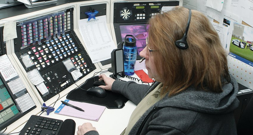 """Telecommunicator Tammy Thompson, at her work station Wednesday morning, has been a dispatcher at the Montgomery County Jail where 911 is currently headquartered for nearly 30 years–longer than there has been 911 service here.  Next to her was telecommunicator Ed Boyd, who has been a dispatcher for 24 years, """"over 50 years between the two of us,"""" Boyd said.  """"That kind of experience is hard to replace."""""""