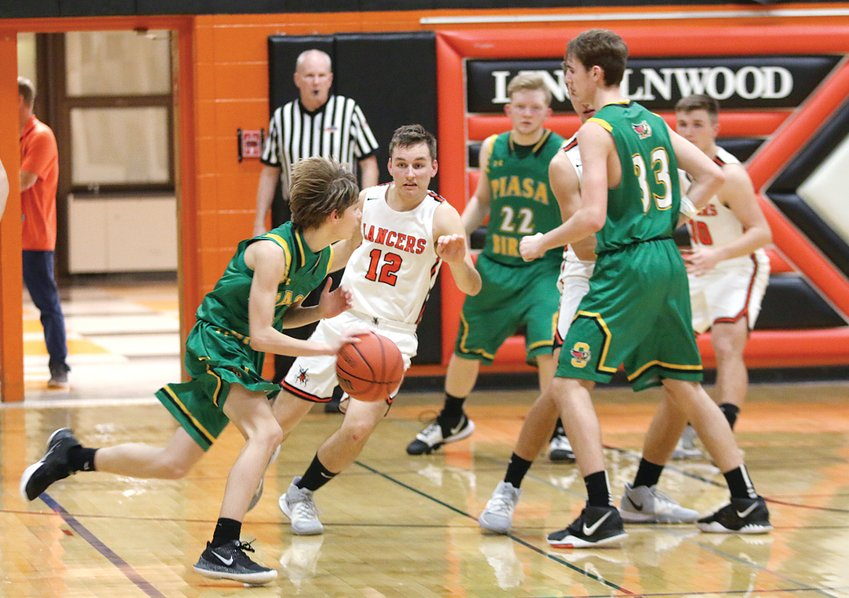 Lincolnwood's Will Jenkins (#12) tracks Southwestern guard Cale Schuchman during the Lancers' home game against the Piasa Birds on Saturday, Dec. 21. The Lincolnwood defense held the Birds to just 12 points in the second half as they scored a 47-35 win over Southwestern, their fifth victory of the season.