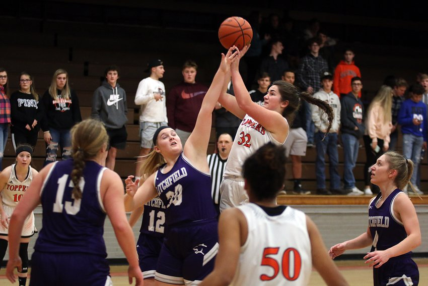 Hillsboro's Emily Reynolds puts a shot up over the outstretched hand of Litchfield's Carly Boden during the South Central Conference game between the two rivals on Jan. 9. The two seniors would lead their respective clubs in scoring, with Boden netting a game-high 14 points and Reynolds putting in 12 in the Toppers' 54-36 victory over the Lady Panthers.