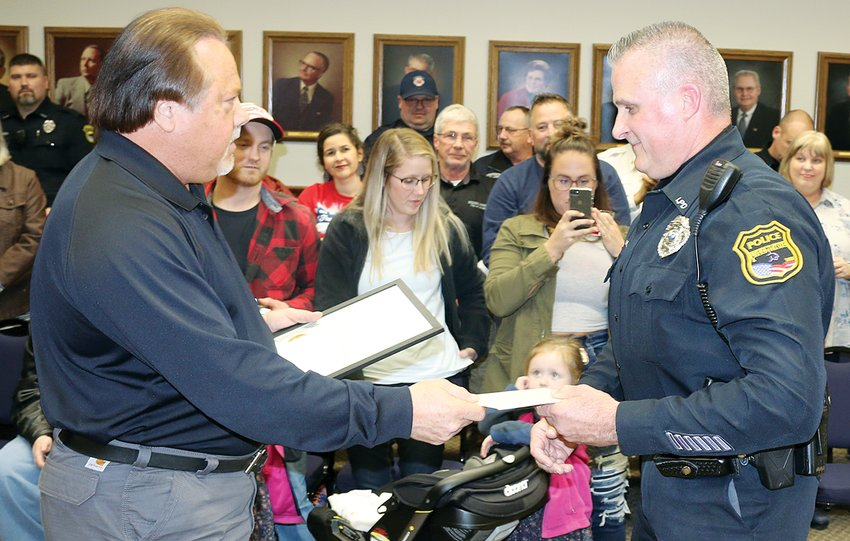 With his family, friends and co-workers looking on, Litchfield Police Officer Brian Maxwell receives a proclamation in honor of his retirement after 20 years with the department from Litchfield Mayor Steve Dougherty.