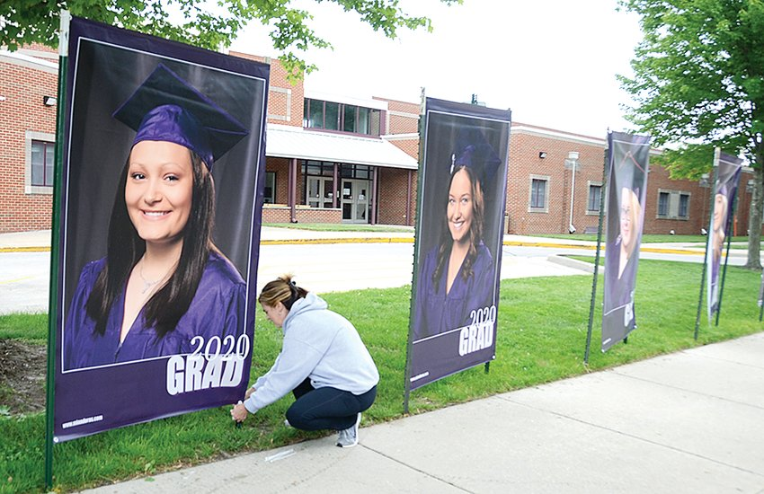 Litchfield School District Curriculum Coordinator Jennifer Thompson works on installing banners of each LHS senior outside the high school on Thursday evening. The district bought a five-foot by seven-foot banner for each senior, and photos for the project were taken by Minndora's Specialty Photography in Litchfield.