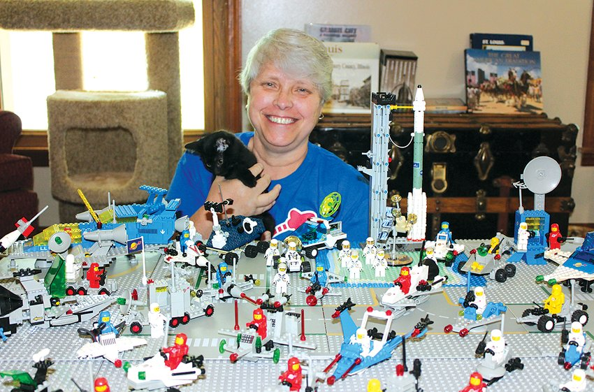 Hillsboro resident Mary Ellen Mathews–who took her mask off for the photo–and her foster kitten are pictured above, in front of her space display made up of 35 Lego sets. According to Mathews, all of the Lego sets above, originate from the 1980s with the exception of a few pieces.