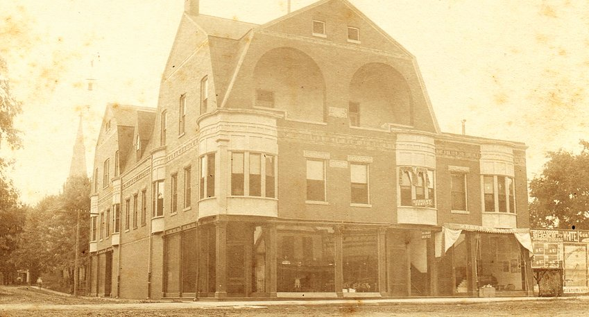 In a photo taken before the streets of downtown Hillsboro were paved, the iconic Corner Block building was erected in 1894 with third floor balconies and a diagonal southeast entrance.