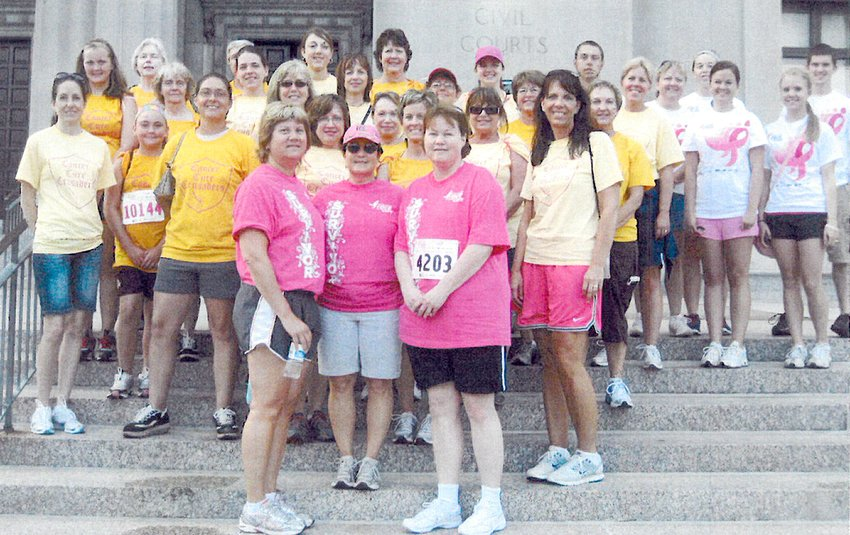 "Julie Timmermann, center, was diagnosed with breast cancer in 2003. After beating it, she took a bus of ""Cancer Crusaders"" to the Susan G. Komen Race in St. Louis, MO, for several years in a row. Timmermann is pictured in the center of the front row."