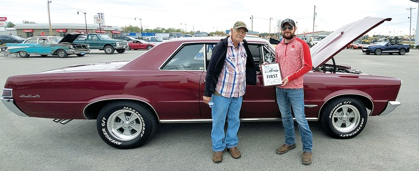 Brian Hendricks of Hillsboro, pictured with his father, Brian, Sr., took first place with his 1965 Pontiac GTO in the JK Harbaugh Car Show and Parade, held Sunday, Oct. 18, at Victory Lane Ford in Litchfield. The show was held to benefit Jeff Harbaugh, who was diagnosed with Ewing Sarcoma in July of this year and has been undergoing treatment.