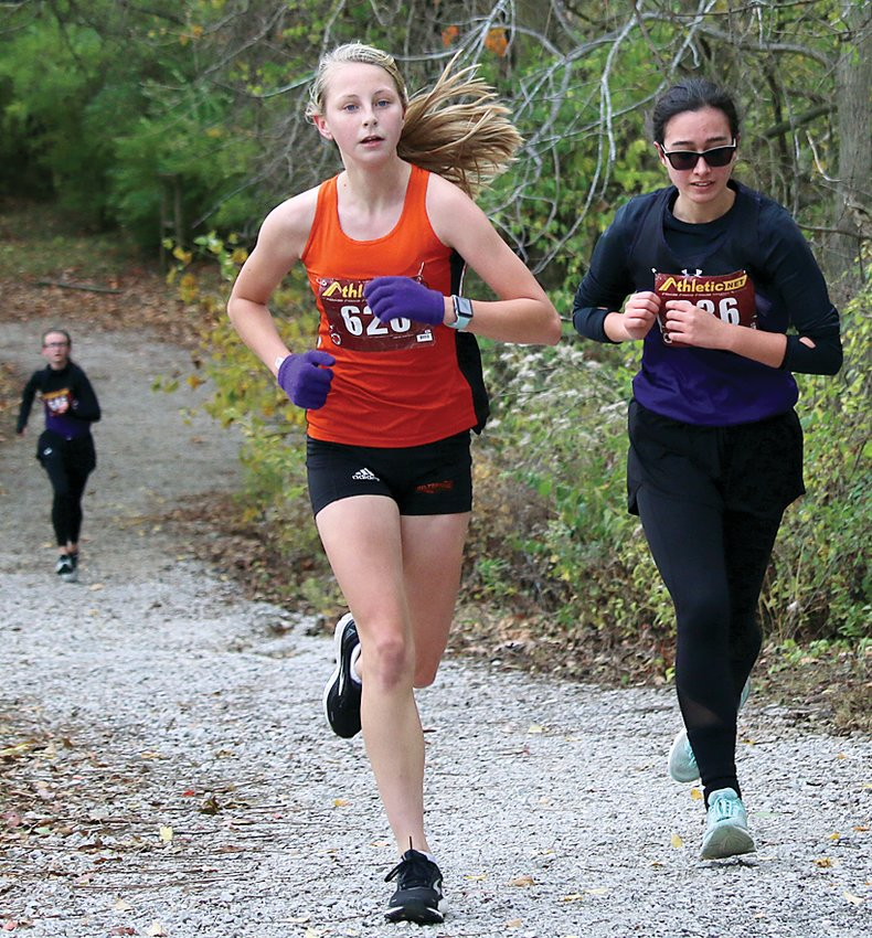 With teammate Delanie Ulrich gaining ground at the bottom of the hill, Litchfield's Myka Fenton (right) races Hillsboro's Sierra Compton up the hill at Loveless Park at the Class 1A Carlinville Regional on Oct. 24. All three girls would advance to sectionals, Compton as an individual by virtue of her ninth place finish and Ulrich and Fenton through the Panthers' fourth place team finish.