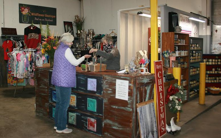 Above, Kim Taylor checks out customers during the grand opening of Taylor Trading Co.'s new location in Nokomis.