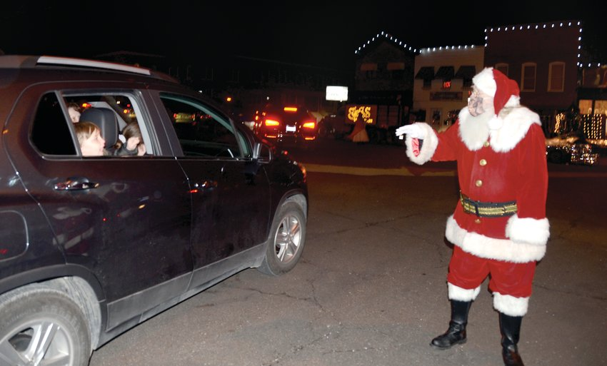 Santa Claus is coming to town! For nearly two hours, a steady stream of cars filled downtown Hillsboro with youngsters of all ages hoping to catch a glimpse of the jolly old elf and many of his helpers. Due to the ongoing pandemic, Imagine Hillsboro volunteers planned a reverse lighted parade on Saturday evening, Dec. 5. Participants parked beautifully decorated floats around the Courthouse Square and cars drove around to see the festive display. Pictured above, Santa Claus greets youngsters in cars from his spot by the Hillsboro Fire Department truck.
