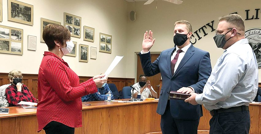 "Litchfield City Clerk Carol Burke swears in Larry ""Bo"" Davis as the newest member of the Litchfield Police Department during the city council meeting on Thursday, Dec. 3. Davis, who was accompanied by his parents, Pam and Larry Davis, the latter of whom helped with the swearing in, is a graduate of Staunton High School and Illinois College."