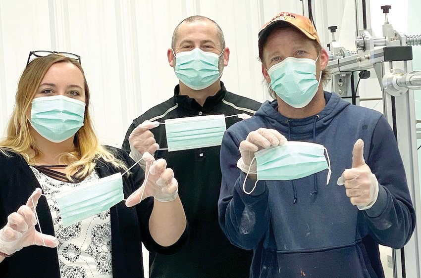 International Filter team members, from the left, Breanne Mayberry, Troy Burris and Phil Anglin show off some of the new face masks the company started making this year at their Litchfield plant. The company plans to roll out full production on the masks in January.