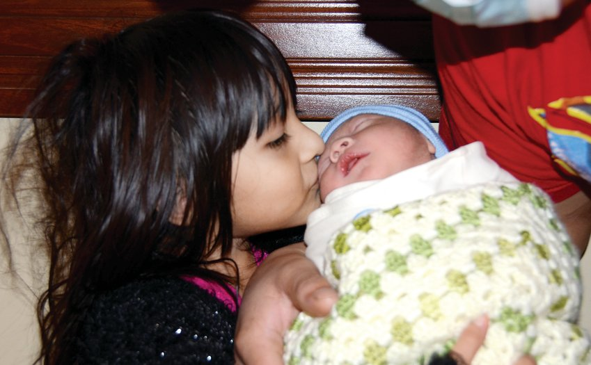 """Alex Alonzo Perez of Litchfield gets a kiss from his big sister, Elena Alonzo Perez, at HSHS St. Francis Hospital in Litchfield. Born on Jan. 1, Alonzo-Perez is the winner of this year's The Journal-News """"First Baby of the Year"""" contest. Their parents are Juan and Juana Alonzo Perez of Litchfield"""