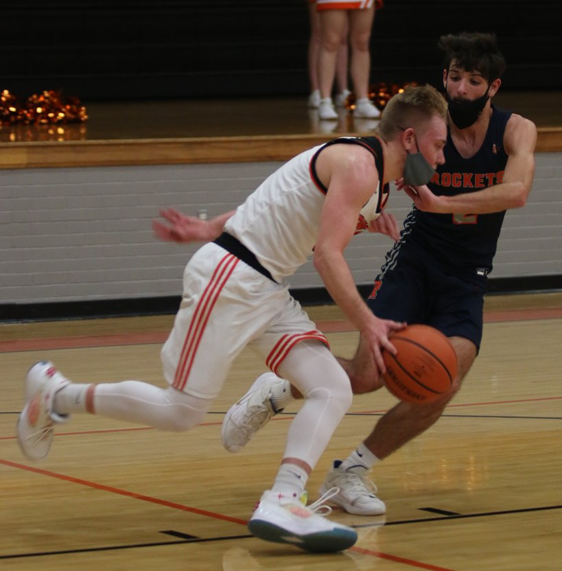 Hillsboro senior Jace Tuetken drives past Rochester defender Brady Butler during the Toppers' first home game of the season on Monday, Feb. 8. Tuetken had 12 points in the Hiltoppers' second win of the season, a 65-56 victory over the Rockets.