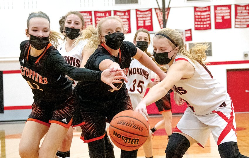 From the left, Hillsboro's Layne Rupert and Claire Tester and Nokomis' Addison Dangbar lunge for a loose ball during Feb. 20's intra-county clash. Rupert and Tester would be two of the four Hillsboro players in double figures as the Lady Hiltoppers snapped Nokomis' five game win streak with a 64-31 victory.