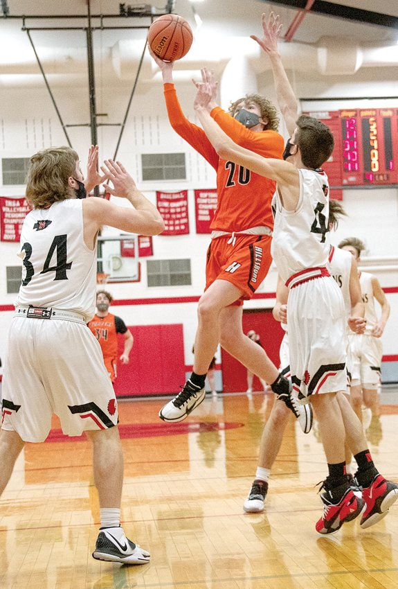 Hillsboro's Drake Vogel cuts between Nokomis' Jake Johnson (#34) and Reece Lohman (#44) for two of his game-high 39 points in the Toppers' 70-56 victory over the Redskins on Saturday, Feb. 20.