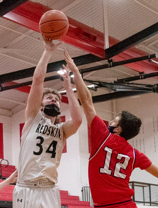 Nokomis' Jake Johnson shoots over the top of Calvary's Brennan Crowder during the Redskins' home game against the Saints on Tuesday, March 9. Johnson had 15 points in the Redskins' 66-37 win over the Saints, one point shy of the team lead, held by Seth Johnson with 16.
