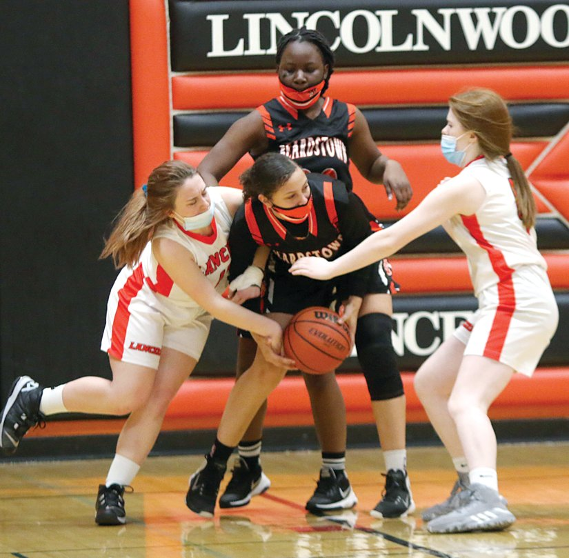 Lincolnwood's Mary Anderson and Amanda Seelbach attempt to force a turnover during the Lady Lancers' final game of the season on Saturday, March 13, against Beardstown.
