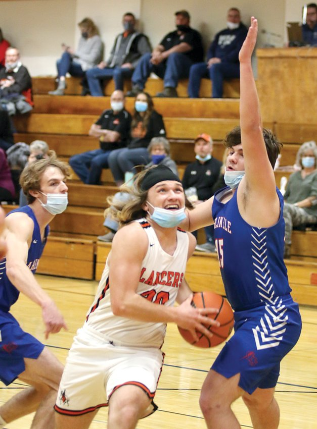 Lincolnwood's Cole Sidwell splits the Carlinville defense on his way to the hoop in the Lancers' 52-33 victory over the Cavies on Friday, March 12.