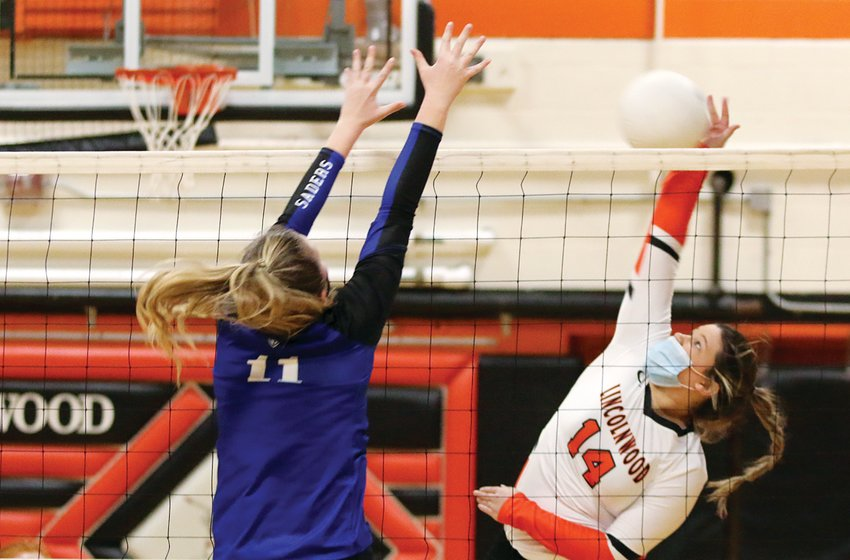 With Lutheran's Paige Bergschneider blocking her view, Lincolnwood's Desi Pitchford elevates for a hit during the Lancers' home game against the Crusaders on Tuesday, March 23.