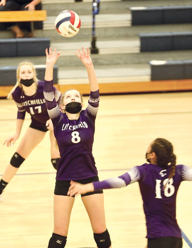 Litchfield's Carlee Harmon (17) and Becky Painter (18) watch as teammate Emma Walch puts a set near the net during the Panthers' game with Greenville on Monday, April 5. The Panthers would lose to the Comets in two, including a marathon 32-30 first game on Greenville's home court.