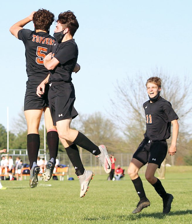 Hillsboro's Ethan Lentz (#5) and Will Christian celebrate Lentz's goal against Carlinville, with Kennon Beecher (#11) coming to join the celebration. Lentz's goal would be the second of three Hillsboro would collect as the Toppers handed the Cavies a 3-0 loss, their first conference loss of the season.