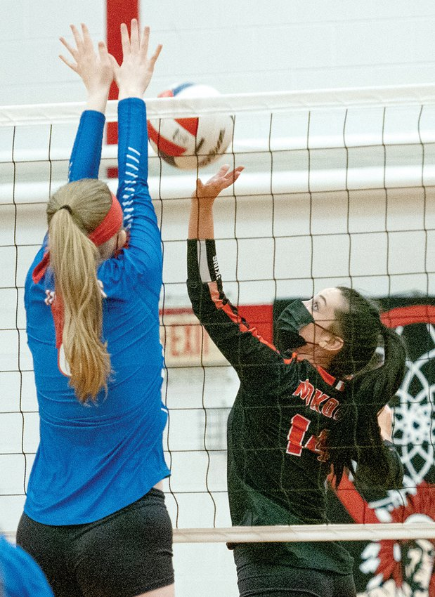 Nokomis' Presley Lamb tries to tip a shot over the Pawnee block during the Lady Redskins' three-game loss to the Indians on Monday, April 12, in Nokomis.