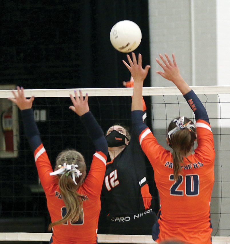 Hillsboro senior Emma Miller tries to slip a spike past the block of Pana during the Toppers' final South Central Conference game of the season on Monday, April 12.