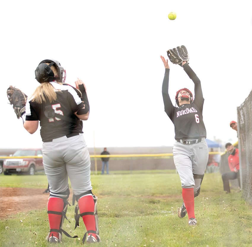 With the Nokomis coaches peering out from the dugout, Kristen Stauder calls off catcher Emma Hill during the Redskins' opening game on Saturday, April 24. The Redskins would keep it close early, but fell to Staunton 11-0 in five innings after a seven-run fifth by the Bulldogs.