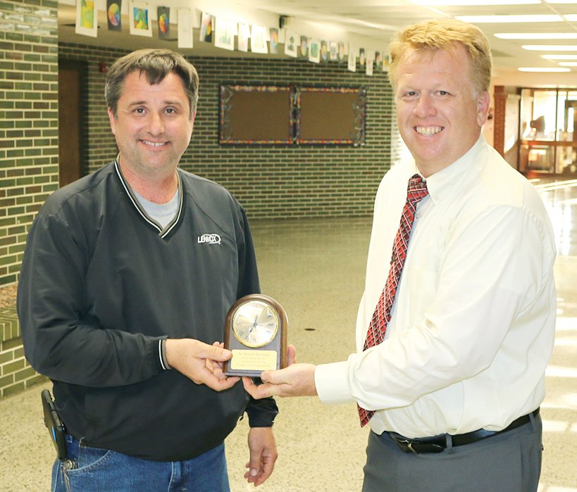 Retiring Panhandle School Board member Rick Bormida, left, is congratulated by Superintendent Aaron Hopper, right.