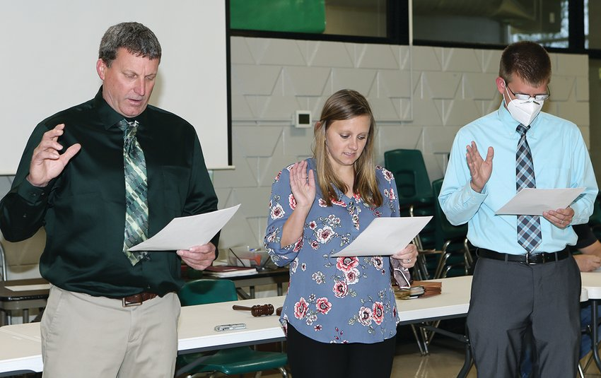 Taking the oath of office, from the left are John Lentz, Kassie Greenwood and Dr. Nathan Kirby.