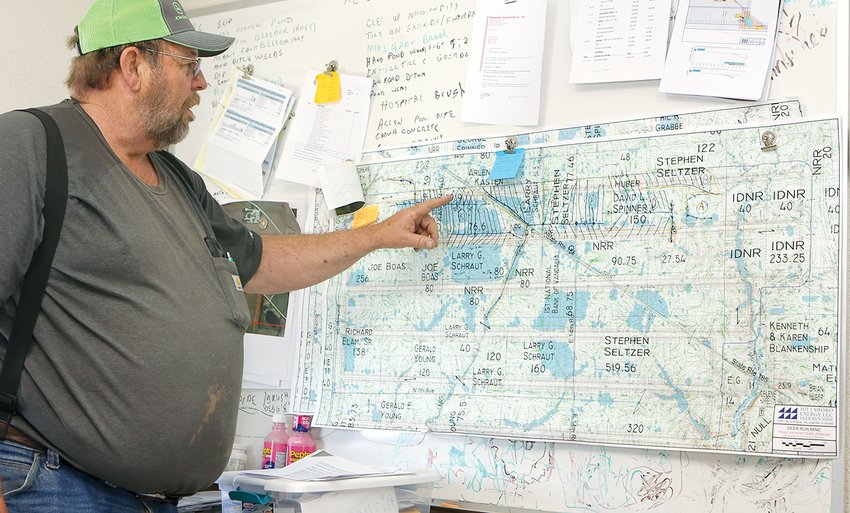 Inside the E&G Construction office in Coffeen, Gerry Spinner goes over hydrological maps that show natural water drainage and where water will pool in the event of a two-and-a-half-inch 24-hour rain.