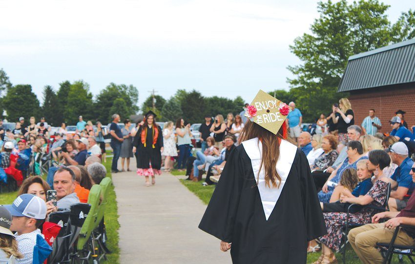 """Graduating seniors lined up inside Lincolnwood High School before making their way to their seats for commencement. Above, Cassie Krager's graduation cap is a friendly reminder to her graduating class–and those around her–to simply """"enjoy the ride."""""""