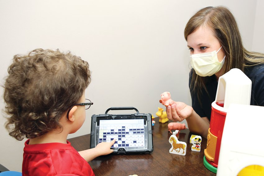 Above, five-year-old Valor Braye of Nokomis uses his LAMP device to ask speech language pathologist Lauren Fuller for a farmyard pig during a session at Teamwork Rehab in Hillsboro.