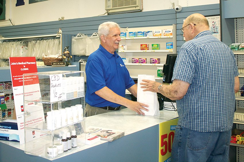 Above, John DalPozzo fills prescriptions and says goodbye to customers prior to the closure of John's Medical Pharmacy on Wednesday, July 7.